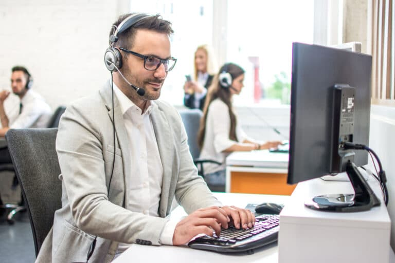 A man wearing glasses and a headset answers support requests on a computer